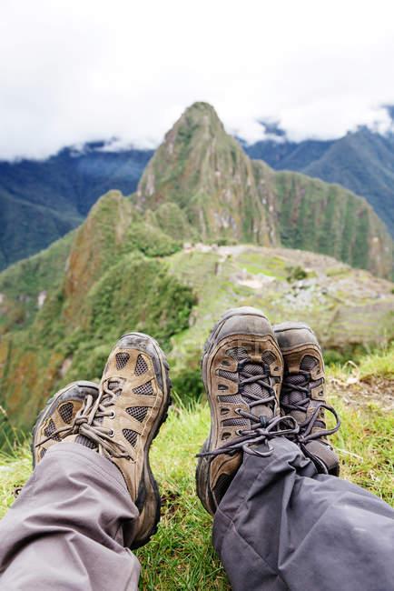Perù, regione di Machu Picchu, stivali dei viaggiatori seduti con vista sulla cittadella di Machu Picchu e la montagna di Huayna — Foto stock