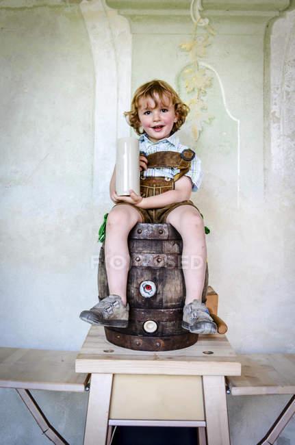 Germany, Bavaria, portrait of smiling little boy sitting on wooden barrel holding beer mug — Stock Photo