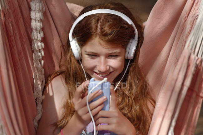 Portrait de fille avec écouteurs et smartphone dans un hamac — Photo de stock