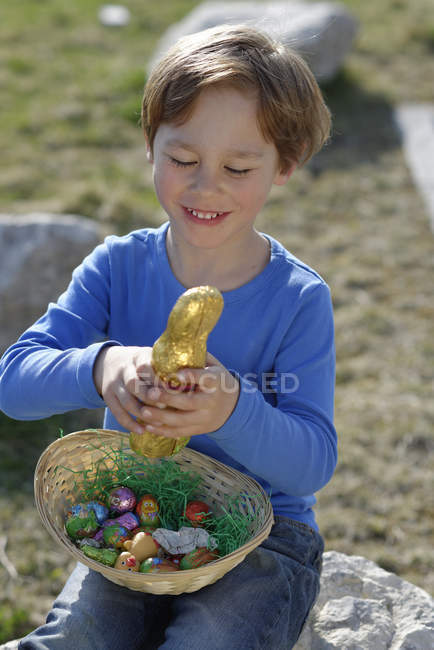 Portrait of smiling little boy with Easter nest and Easter bunny — Stock Photo