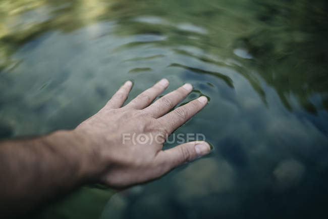 Man's hand touching water surface of a mountain pond — Stock Photo