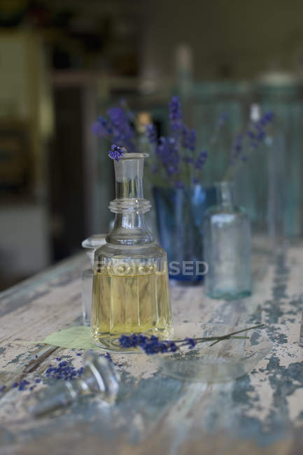Lavender Oil And Flowers In Glass Bottles On Wooden Surface Color