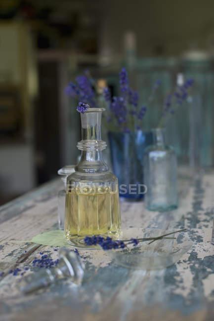Huile de lavande et fleurs en bouteilles de verre sur surface en bois — Photo de stock