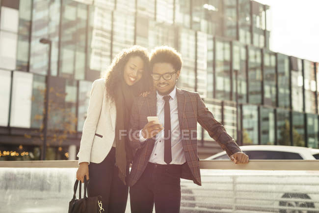 Two smiling young business people outdoors using smartphone — Stock Photo