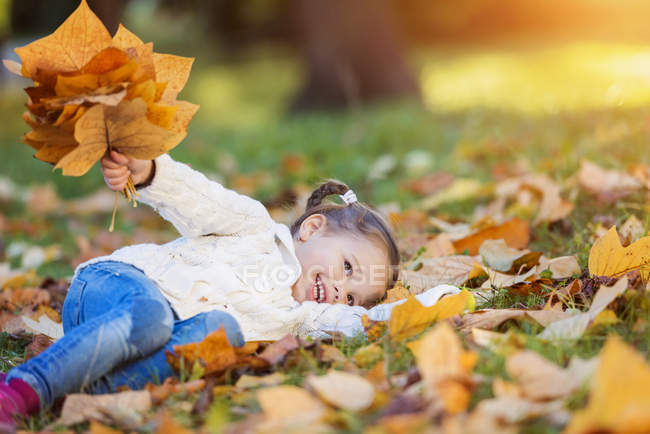 Glückliches Mädchen liegt in herbstlicher Wiese — Stockfoto