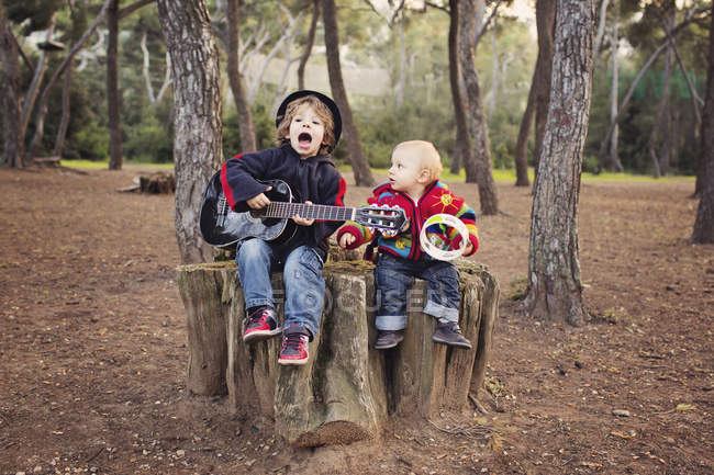 Little boy playing guitar and singing for his baby brother in a forest — Stock Photo
