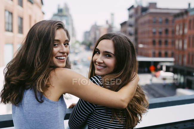 USA, New York City, two friends embracing in the city — Stock Photo