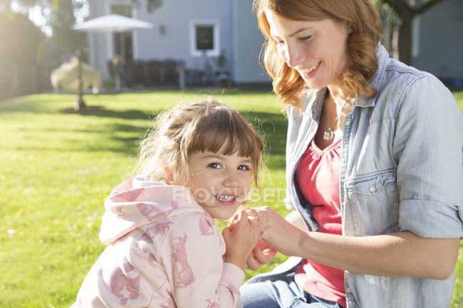 Happy mother with daughter sitting in garden — Stock Photo