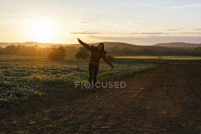 Spain, Catalunya, Girona, woman hiking on field path at sunrise — Stock Photo