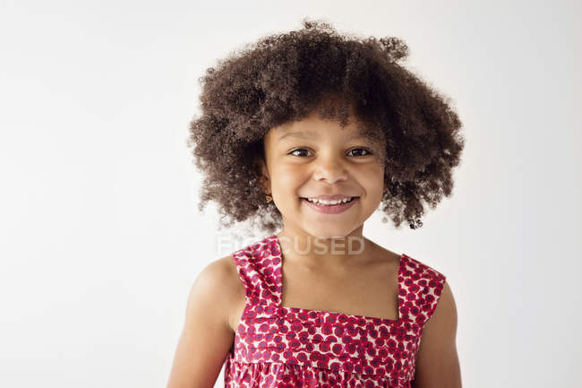 Portrait of smiling little girl with afro in front of white background — Stock Photo