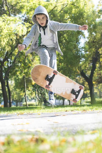 Garçon de faire un truc de skateboard dans le parc — Photo de stock