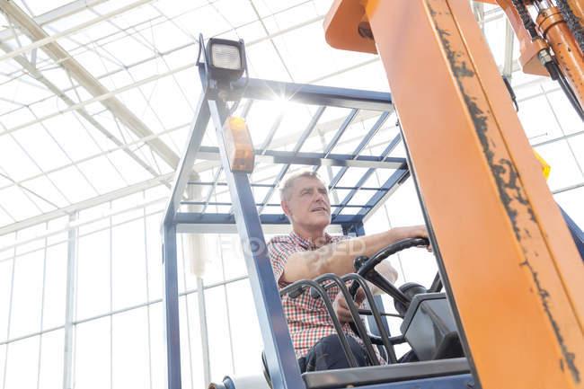 Uomo sul carrello elevatore nel corridoio di vetro — Foto stock