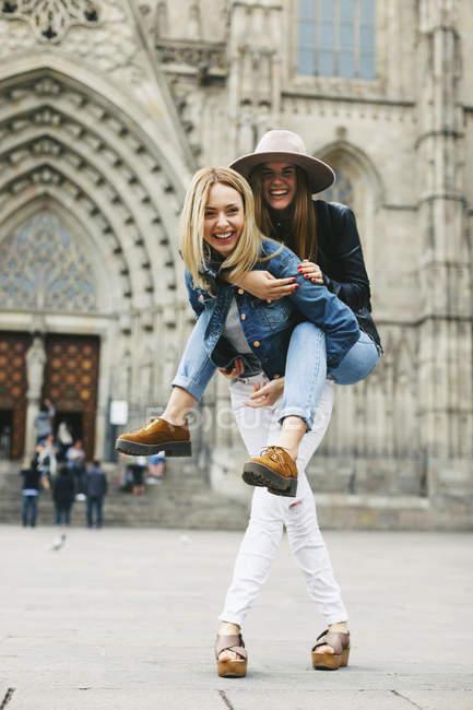 Espagne, Barcelone, heureuse jeune femme portant un ami dans la ville — Photo de stock