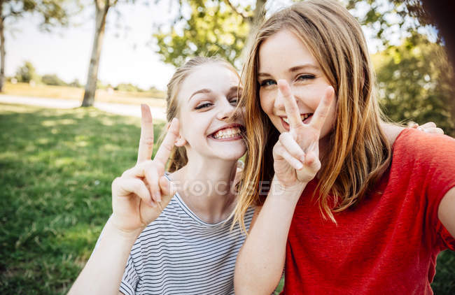 Two playful teenage girls making victory sign — Stock Photo