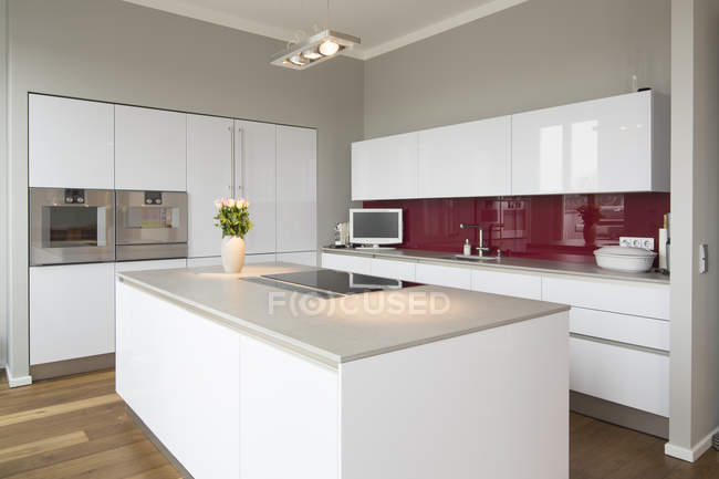 Interior of modern kitchen with freestanding kitchen block and flowers in vase — Stock Photo