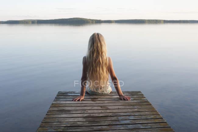Finland, Karelia, Uukuniemi, Lake Pyhjrvi, back view of a girl sitting on jetty — Stock Photo