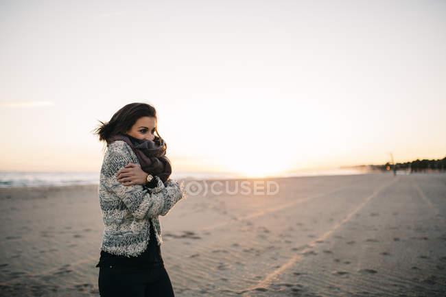 Donna che si congela sulla spiaggia in inverno — Foto stock