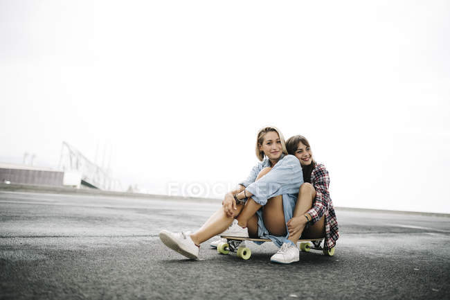 Two young women sitting on a longboard — Stock Photo