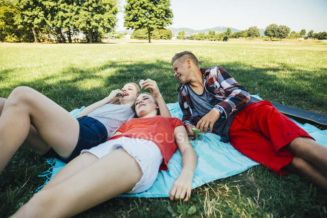 Three teenage friends relaxing in meadow — Stock Photo