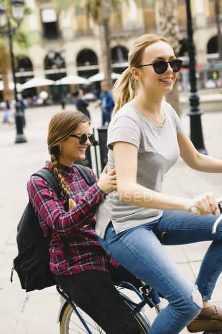 Due giovani donne felici che condividono la bicicletta in città — Foto stock