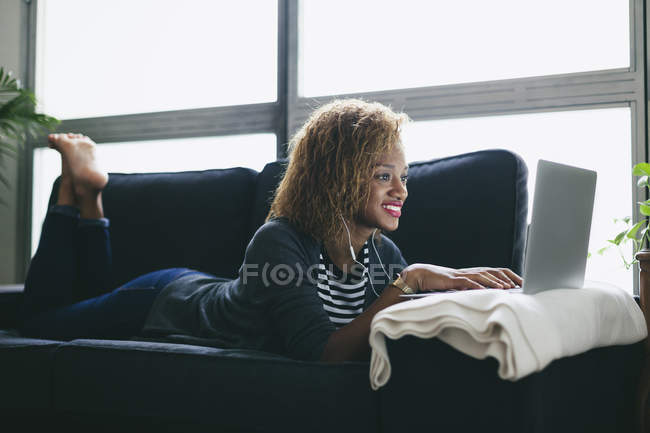 Woman lying on couch with earphones — Stock Photo