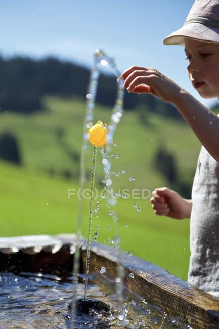 Menino brincando com uma pequena bola na fonte — Fotografia de Stock