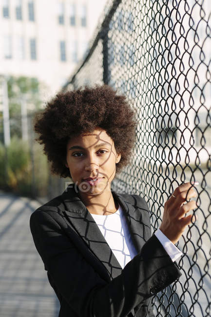 Portrait of businesswoman standing beside mesh wire fence — Stock Photo