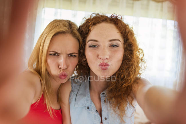 Portrait of two female friends pouting mouths while looking at camera — Stock Photo