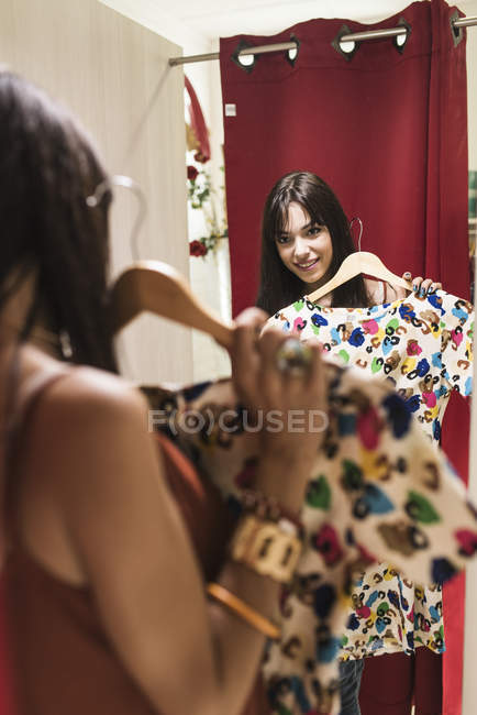 Young woman in fashion boutique trying on dress — Stock Photo