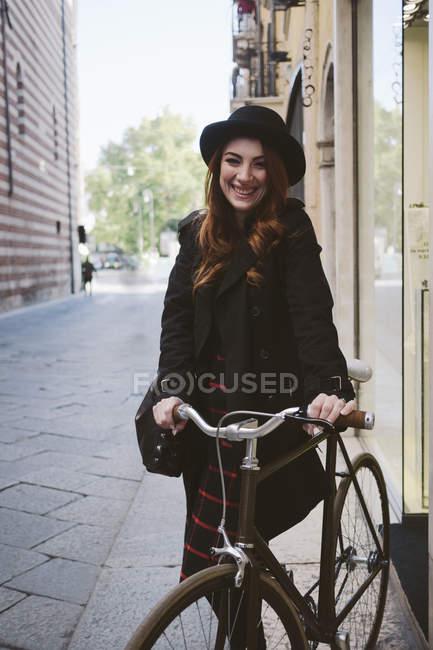 Italie, Vérone, heureuse jeune femme avec vélo dans la ville — Photo de stock