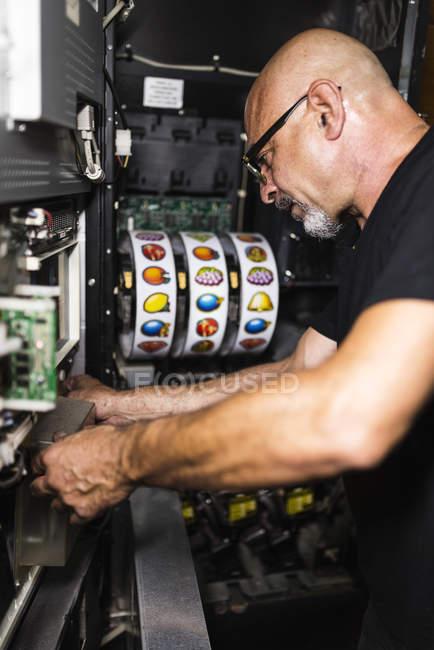 Technicien travaillant à la machine à sous — Photo de stock