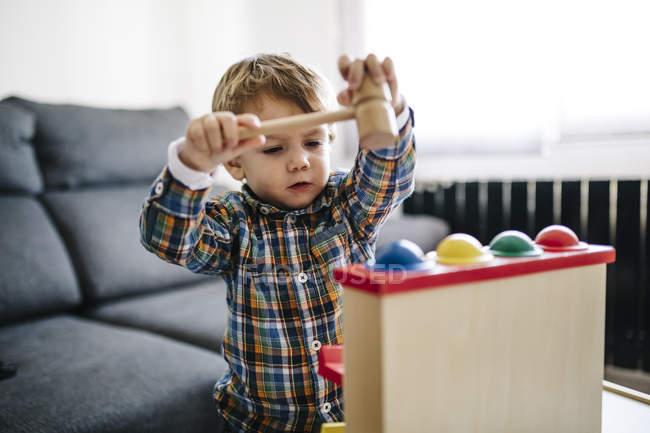 Мальчик играет с деревянной игрушкой моторики — стоковое фото