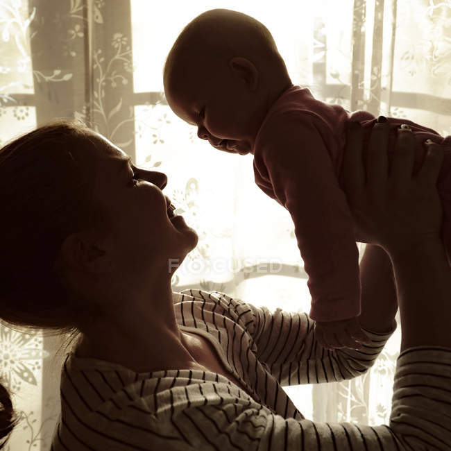 Mother holding baby up in air in front of a window — Stock Photo