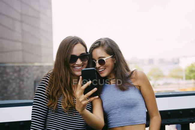 Dois amigos sorridentes olhando para o telefone celular — Fotografia de Stock