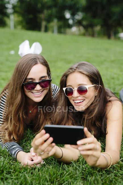 Due amici felici in un parco che guardano il cellulare — Foto stock