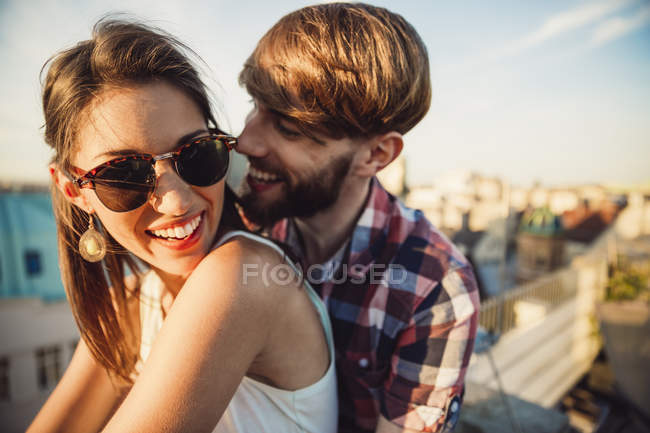 Young couple enjoying romantic sunset on rooftop terrace — Stock Photo