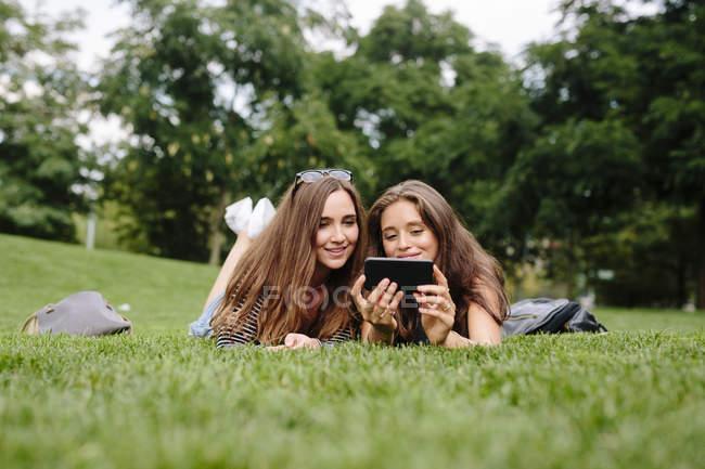Двоє друзів в парку, дивлячись на мобільний телефон — стокове фото