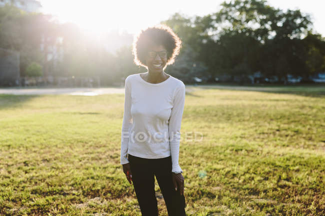 Smiling young woman standing on a meadow of a park at backlight — Stock Photo