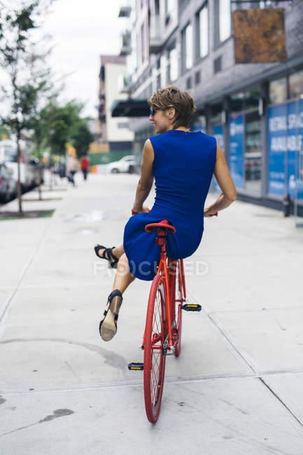 Back view de mulher loira sorridente equilibrando na bicicleta vermelha — Fotografia de Stock