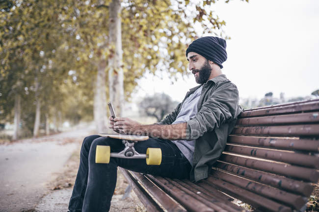 Man with longboard using smartphone — Stock Photo