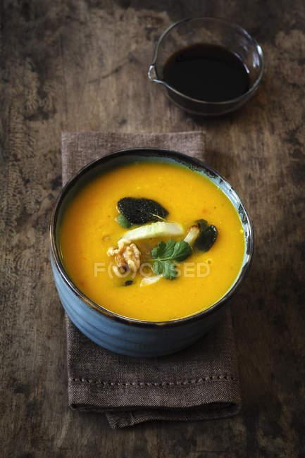 Чаша веганский крем суп из тыквы с грецкими орехами и соевый соус — стоковое фото