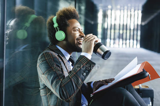 Smiling young businessman with coffee to go mug, headphones and folder outdoors — Stock Photo