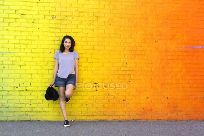 Porträt einer lächelnden jungen Frau, die sich an eine gelbe Ziegelwand lehnt — Stockfoto