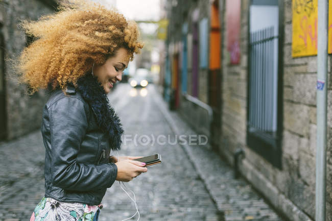 Smiling woman with afro hair looking at her smartphone — Stock Photo