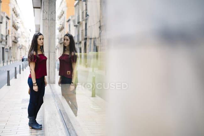 Молодая женщина в городе смотрит в витрину магазина — стоковое фото