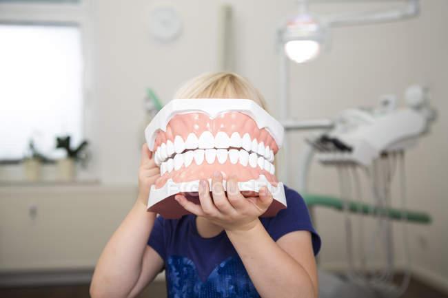 Ragazza in chirurgia dentale in possesso di grande modello di dente — Foto stock