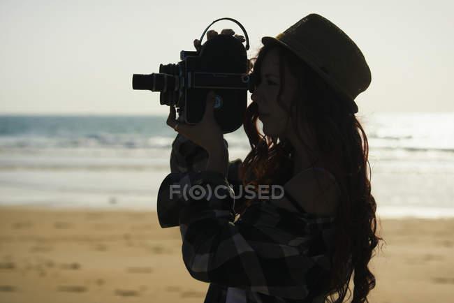Силует молоду жінку, використання старого фільму камера на пляжі — стокове фото