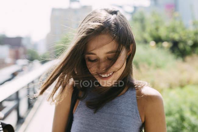 Улыбающаяся брюнетка молодая женщина на открытом воздухе — стоковое фото