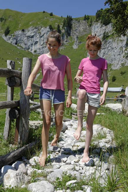 Alemania, Baviera, Lenggries, dos chicas caminando descalzas por camino de piedra en el pasto de la montaña en la montaña Brauneck - foto de stock