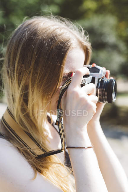 Blond young woman photographing outdoors — Stock Photo